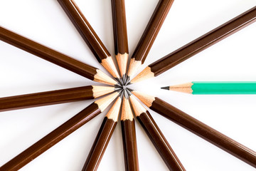 brown wooden pencil arrange as circular with one  different pen