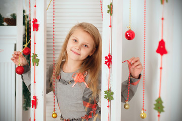 Little girl waiting for a miracle in Christmas decorations