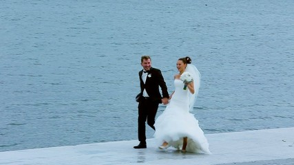 Bride and groom running along the waterfront