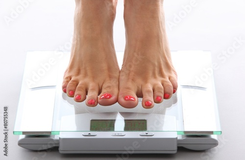 Leinwanddruck Bild woman feet on a bathroom scale