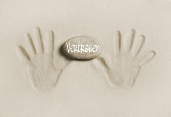 Hände: Sand mit Stein und Text Vertrauen: Konzept Partnerschaft