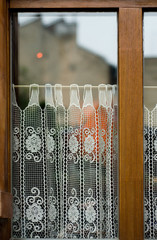 Old window with wooden frame lacy curtain and house reflection