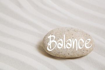 Wort Balance auf Stein im Sand als Hintergrund für Wellness