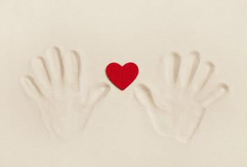 Zwei Hände im Sand halten ein rotes Herz