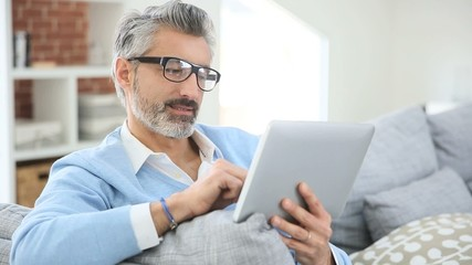 Mature man with eyeglasses websurfing on tablet at home