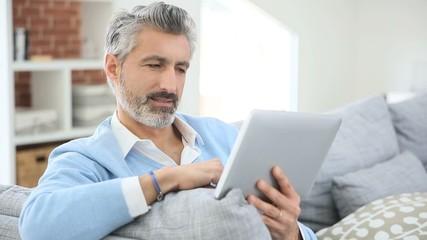 Mature handsome man websurfing on tablet at home