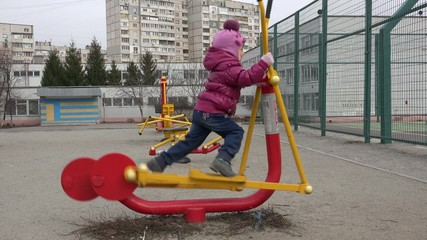 Cute Little Girl Running on Elliptical Trainer in the Open Air