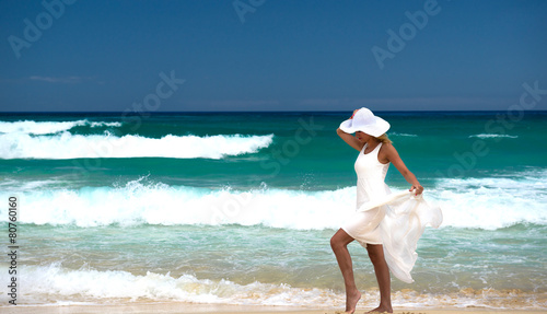 Woman in white dress enjoying sea waves on the beach - 80760160
