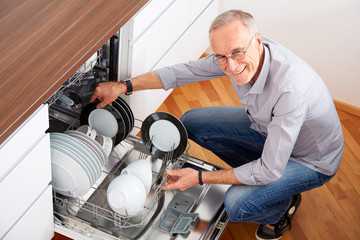 Senior man in kitchen, empty out the dishwasher 2