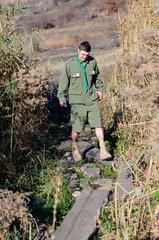 Boy Scout Crossing Creek on Wood Plank Footbridge