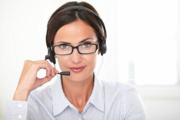Seductive woman receptionist talking on headset