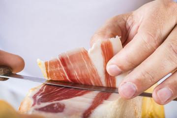 Profesional cortando lonchas de jamón serrano a cuchillo