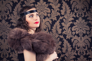 beautiful retro woman posing against vintage wallpapers