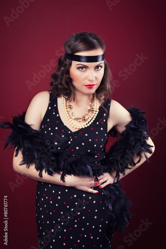 beautiful retro woman posing against wine red background