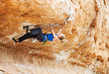 Young female rock climber struggling to make next movement up