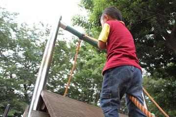 ロープで壁を登る幼児(3歳児)