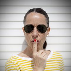 Mujer con jersey amarillo haciendo gesto de silencio