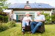 Senior Mann und Frau sitzen vor ihrem Haus