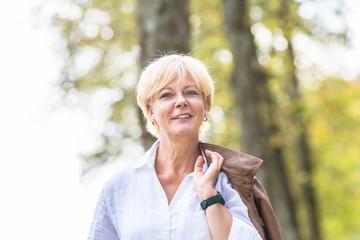 Senior Frau hat Spaß bei Herbst Spaziergang