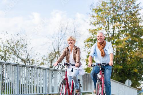 Senioren Paar mit Fahrrädern auf Brücke - 80763515