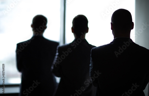 silhouette of three businessmen in the office - 80764109
