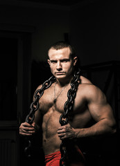 Muscular strong male  poses holding steel chain
