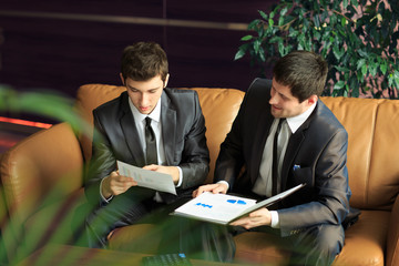 Image of two young businessmen discussing project