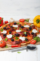 Pizza on wooden table with ham, salami, tomato and chili pepper