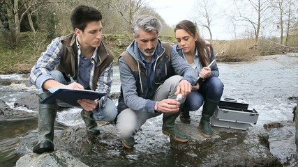 Biologist with students in science testing river water