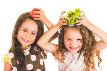 Beautiful healthy little girls holding fruits and vegetables on