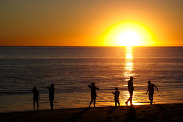 Family playing on beach and silhouetted by sunset