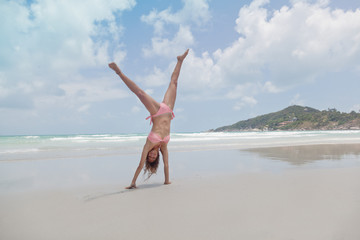 Beautiful young woman standing on hands on the beach