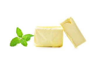 Stick of butter and mint leaves isolated on white.