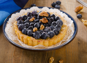 Tasty tart with blueberries  on a wooden table