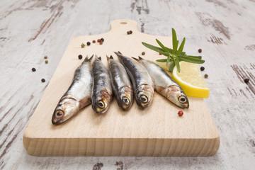 Sardines on wooden kitchen board.