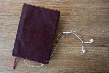 Contemporary image of a Bible with headphones. Hearing the voice