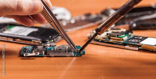 Leinwanddruck Bild employee repairing fractured phone