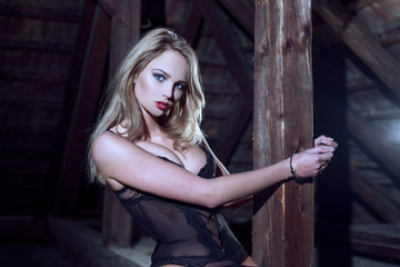Sexy blonde woman cuffed to timber at barn