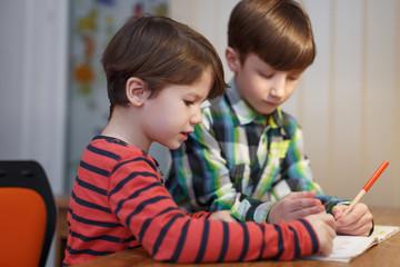Little boys study math together at desk