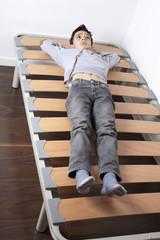 Niño tumbado en somier