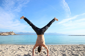 man doing handstand on the beach