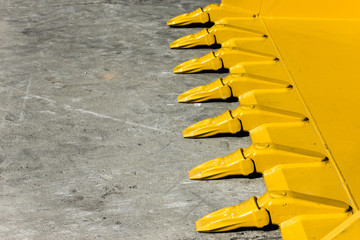Big yellow bucket scoop on rough concrete ground.