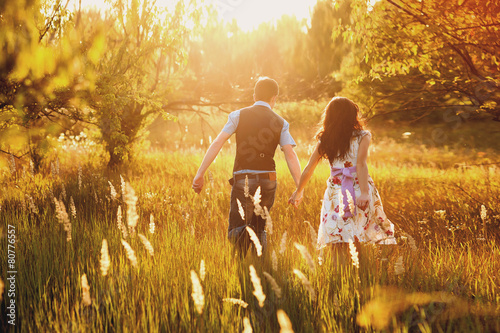 Fashionable cool couple runs across the field in sunset light
