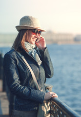 Beautiful woman in hat and scarf with mobile phone in the city