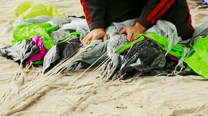 Man Wrapping Parachute Shroud Lines On The Ground