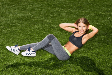 Athletic young woman doing exercises for abdominal muscles