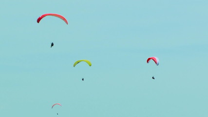 Four Paragliders Slowly Flying In The Blue Sky
