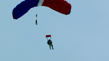 One Parachutist With Blue And Red Chute Slowly Lowering For