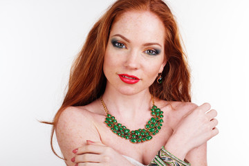 Redheaded girl is wearing green necklace