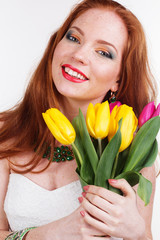 Beautiful redheaded happy girl is holding tulips